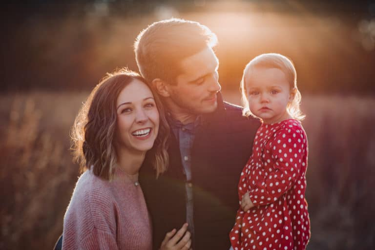 Family of three smiling at sunset